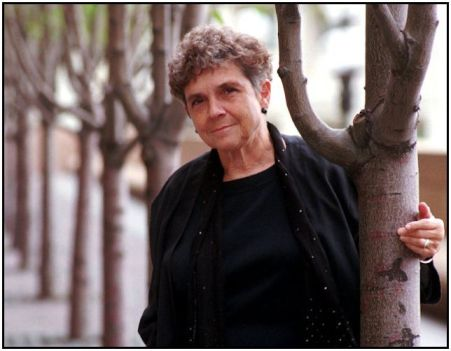 adrienne rich by tree with row of trees behind her