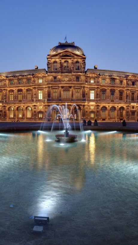 paris louvre palace at night water in foreground