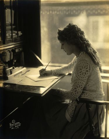 #55 Mary_Pickford at desk writing PROGRESS EXCELLENT
