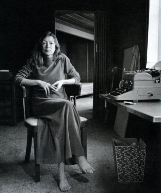 joan didion in chair at desk with typewriter